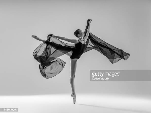 young beautiful dancer dancing on gray background - ballet stock pictures, royalty-free photos & images