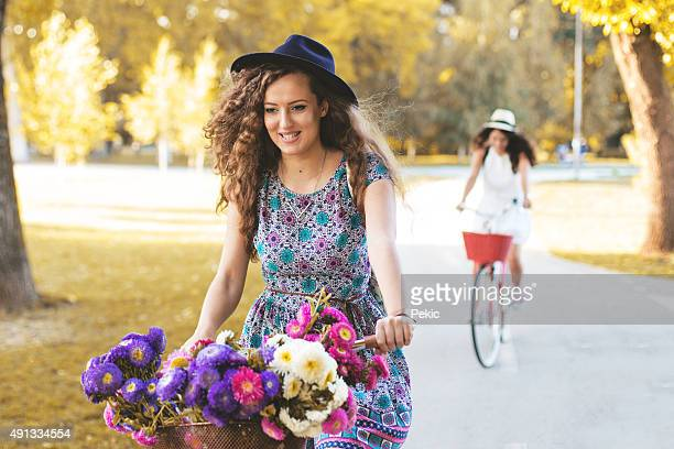 Young beautiful, elegantly dressed girls with bicycles