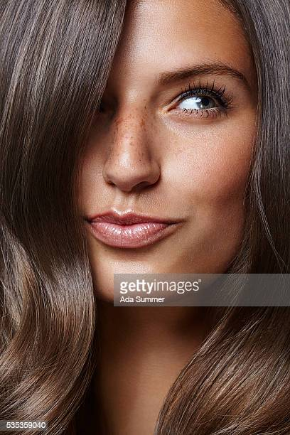 young beautiful female adult with long shiny hair - braun stock-fotos und bilder