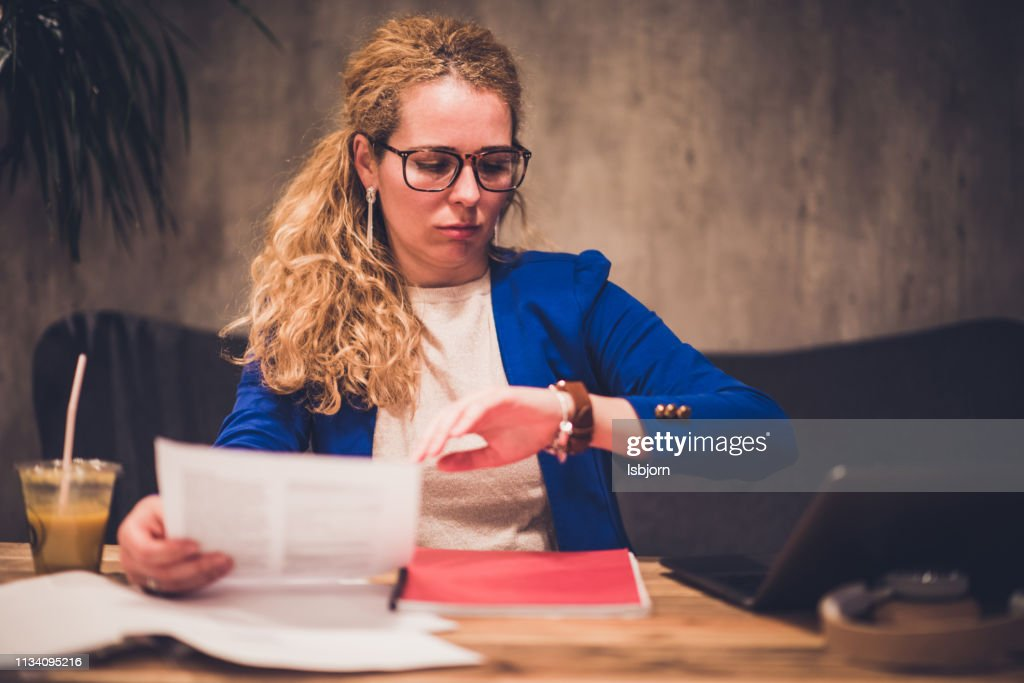 Young beautiful female chasing time. : Stock Photo