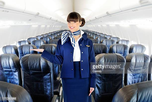 Young beautiful flight attendant welcome