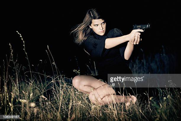 young beautiful girl aiming a gun - shooting crime stock pictures, royalty-free photos & images