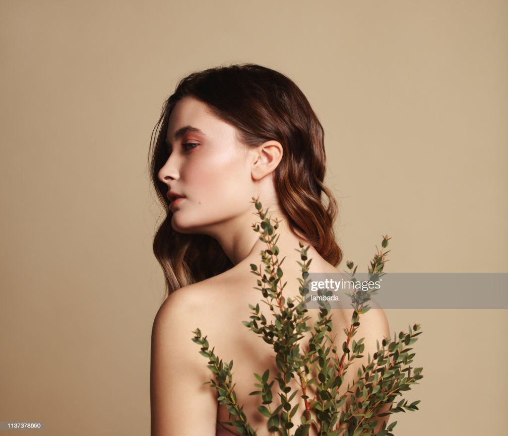 Young beautiful girl and plant : Stock Photo
