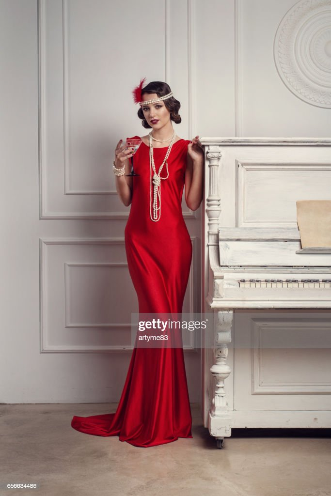 Young beautiful girl in red dress style of the 20's or 30's with glass of martini near the piano. Vintage style beautiful woman. Old fashioned makeup and retro finger wave hairstyle. : Stock Photo