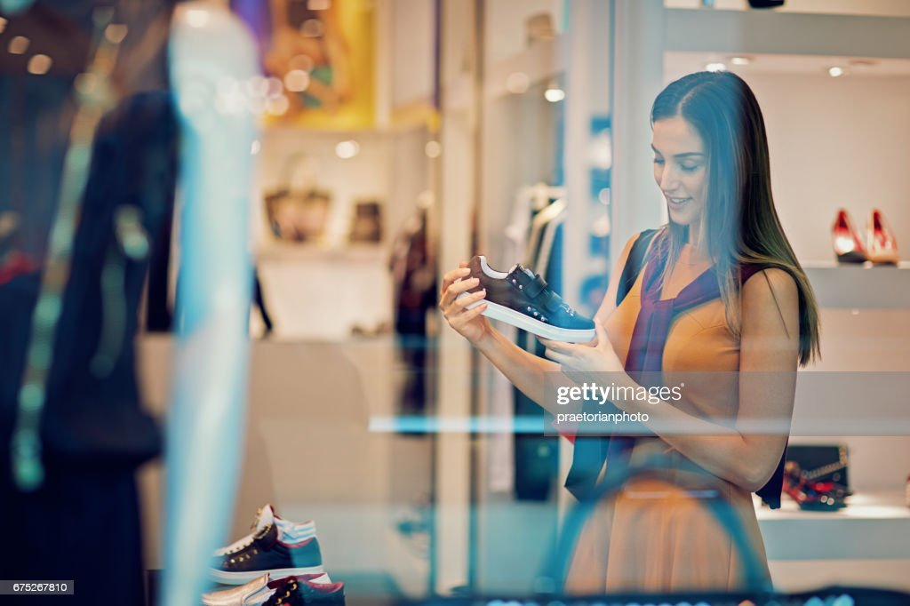 Young beautiful girl is looking shoes in the Mall : Stock Photo