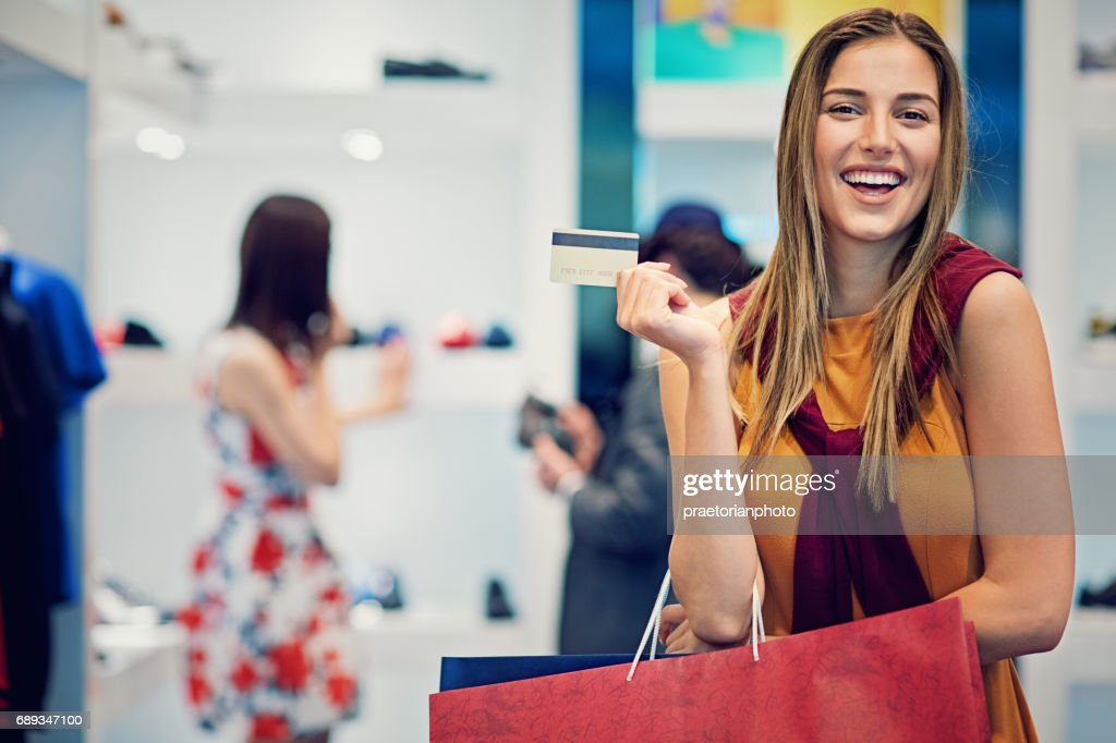 Young beautiful girl is possing with her credit card and shopping bags in the boutique : Stock Photo