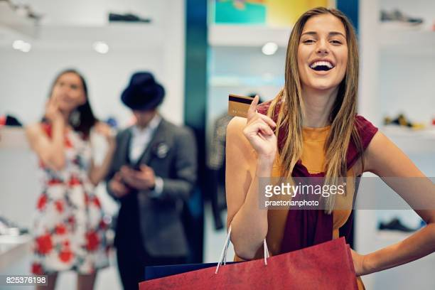 Young beautiful girl is possing with her credit card and shopping bags in the boutique
