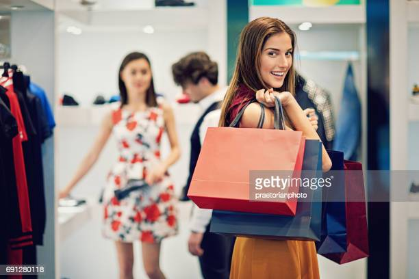 young beautiful girl is possing with her shopping bags in a boutique - shopping bag stock pictures, royalty-free photos & images