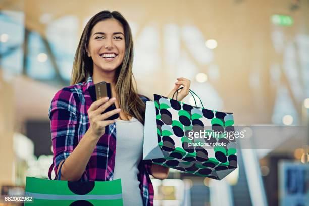 Jovem menina bonita é fazer compras no shopping