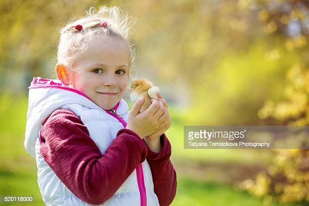Young beautiful girl, playing with little newborn chick in the park, springtime