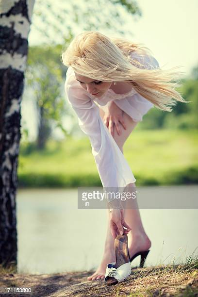 young beautiful girl putting on her shoes - pretty white girl feet stock photos and pictures