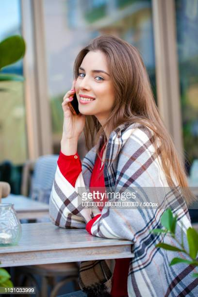 Young Beautiful Girl Sits In Summer Cafe And Calling By Phone