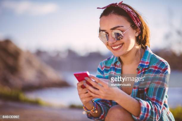 Young beautiful girl smiling and checking her social networks