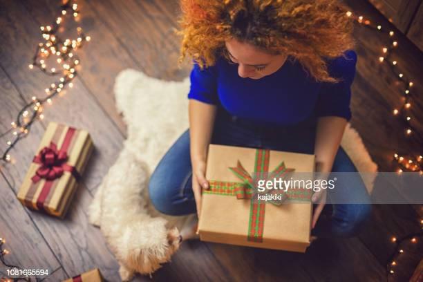 junge schöne mädchen mit gegenwart in eine gemütliche weihnachtsstimmung - dezember stock-fotos und bilder