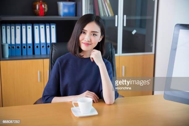美しい少女は、彼女の仕事を始めたオフィスで座っています。