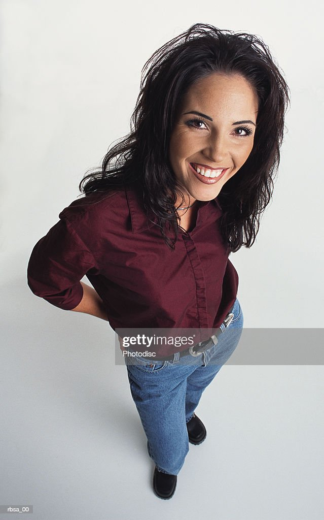young beautiful happy ethnic adult female with long dark hair wearing jeans and a silk blouse looks up at the camera and smiles warmly : Foto de stock