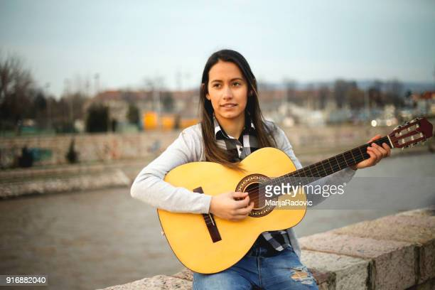 Young beautiful hipster woman. Playing guitar near the river.