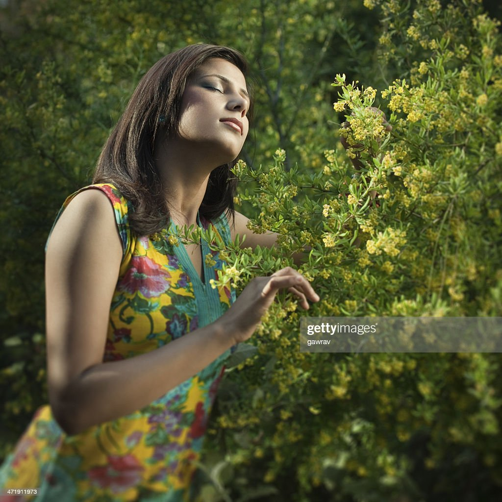 Young, beautiful Indian woman feeling fresh fragrance in blossoming nature. : Stock Photo