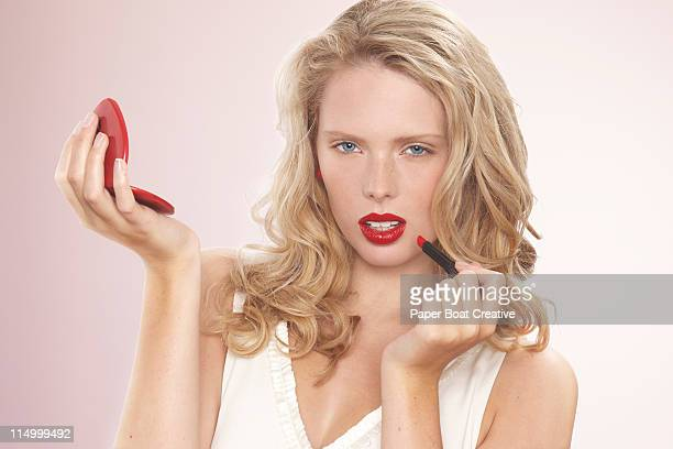 young beautiful lady applying hot red lipstick