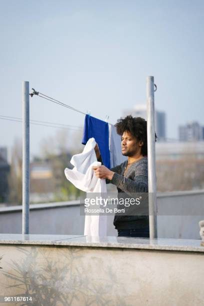 Young beautiful man hanging up laundry on rooftop terrace