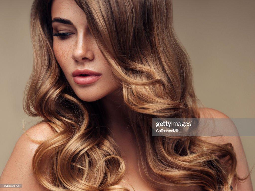 Giovane bella modella con lunghi capelli ondulati ben curati : Foto stock