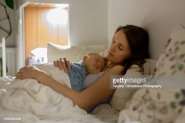 young beautiful mother sleeping her newborn baby boy at night dim light. mom breastfeeding infant - parenting stock pictures, royalty-free photos & images