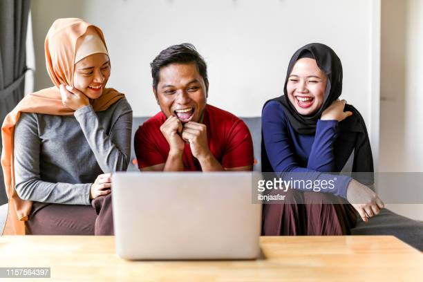 ラップトップを使用して若い美しいイスラム教徒の家族 - 複婚 ストックフォトと画像