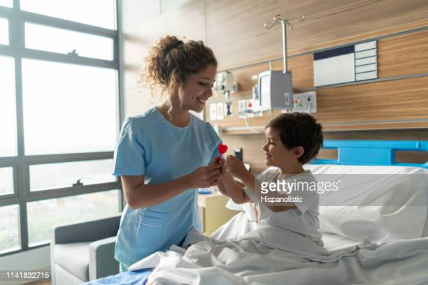 young beautiful nurse giving a lollipop to pediatrics hospitalized patient smiling - cute nurses stock pictures, royalty-free photos & images