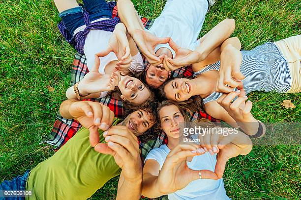 Young beautiful people showing heart sign with hands
