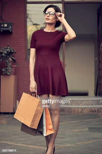 Junge schöne stehend mit Einkaufstaschen