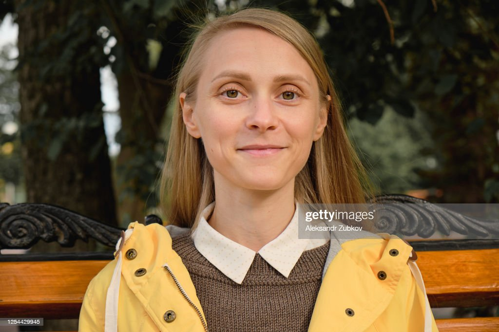 A Young Beautiful Stylish Girl Is Sitting On A Bench In A Public Park On The Street. Portrait Of A Happy Smiling Woman. : Stockfoto