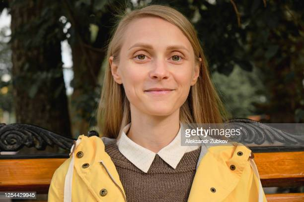 a young beautiful stylish girl is sitting on a bench in a public park on the street. portrait of a happy smiling woman. - rusland stockfoto's en -beelden