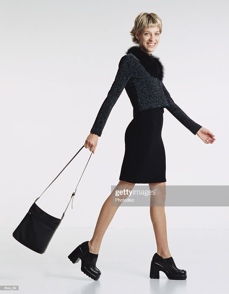 young beautiful thin caucasian adult female wearing trendy dark sweater with fur collar and a short dark skirt and high heels swings a large purse as she walks sideways to the camera turning to smile attractively : Foto de stock