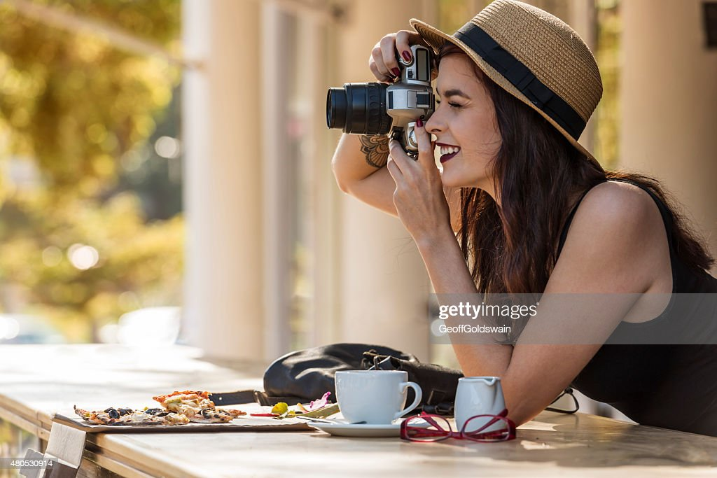 young beautiful traveler happily taking photos with camera at ca : Stockfoto