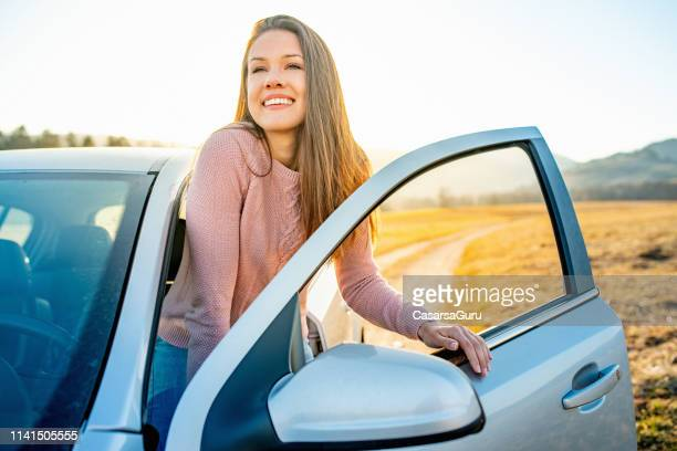 young beautiful woman arrived at her destination by car - disembarking stock pictures, royalty-free photos & images