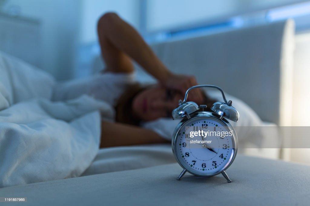 jonge mooie vrouw thuis slaapkamer liggend in bed laat in de nacht proberen te slapen lijden slapeloosheid slaapstoornis of bang op nachtmerries op zoek verdrietig bezorgd en gestrest : Stockfoto