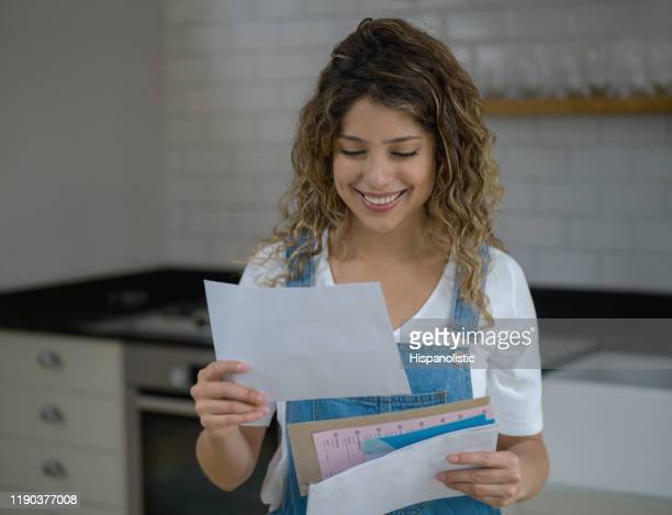 young beautiful woman at home checking her mail looking very happy - message stock pictures, royalty-free photos & images