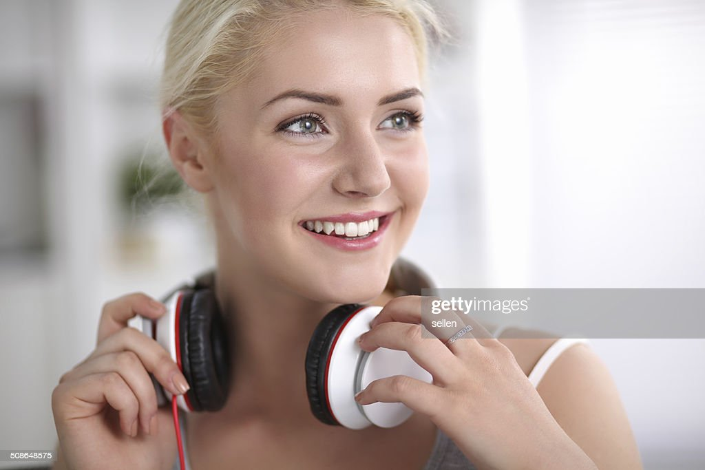 Young beautiful woman at home sitting on sofa and listening : Stock Photo