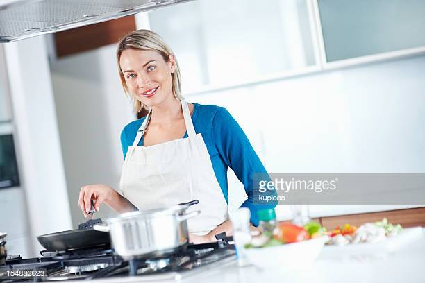 Young beautiful woman cooking food in kitchen