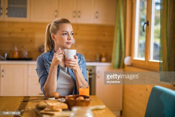 young beautiful woman day dreaming during coffee time at home. - looking away stock pictures, royalty-free photos & images