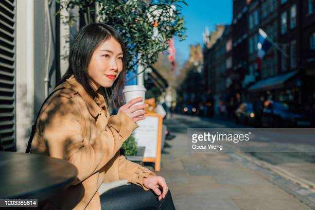 young beautiful woman drinking coffee at outdoor cafe - outdoors stock pictures, royalty-free photos & images