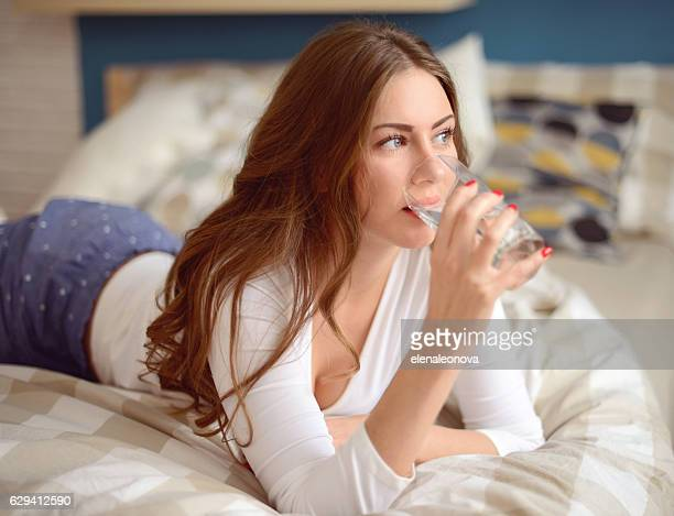 young beautiful woman drinks water from a glass