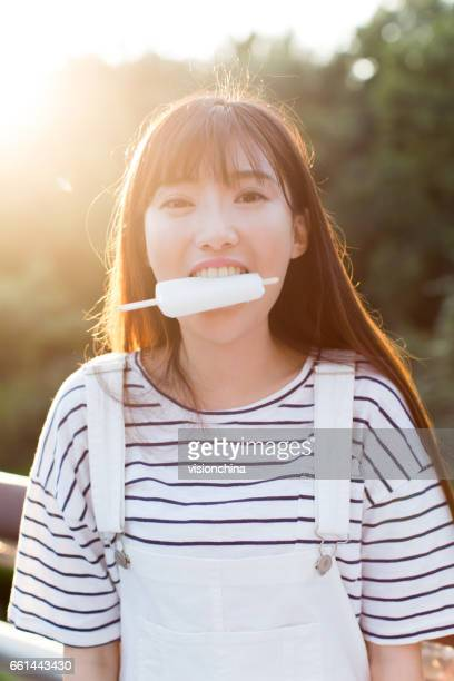 young beautiful woman eating a delicious ice cream in nature - lolly models stock pictures, royalty-free photos & images