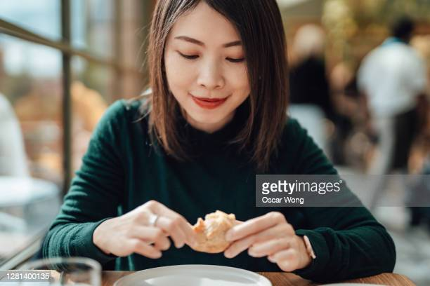 young beautiful woman eating bread at the restaurant - bakery stock pictures, royalty-free photos & images