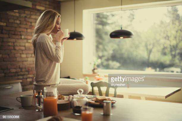 young beautiful woman enjoying in morning coffee in the kitchen. - nightdress stock pictures, royalty-free photos & images