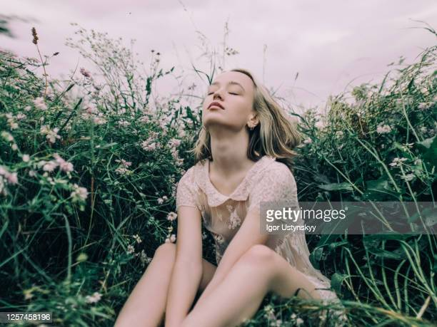 young beautiful woman enjoying the calm meadow - profumo foto e immagini stock