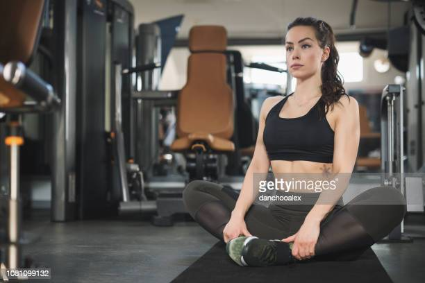 young beautiful woman exercising at the gym - beautiful woman chest stock pictures, royalty-free photos & images