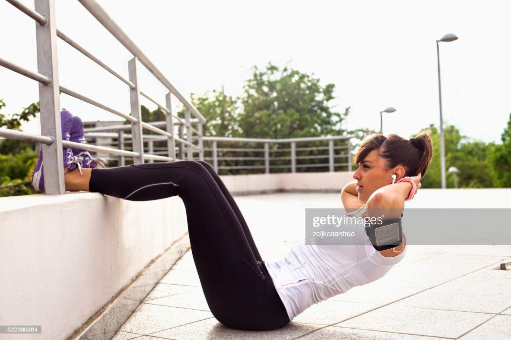 Young beautiful woman exercising outdoors : Stock Photo
