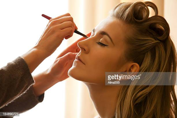 Young beautiful woman getting her makeup applied by MUA