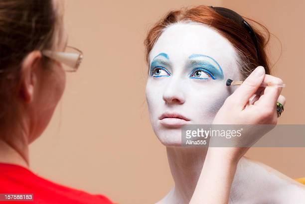 Junge schöne Frau, die Ihr Make-up-Anwendung erhalten von MUA